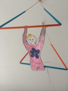 Paper acrobat hanging from a trapeze madeof string and straws